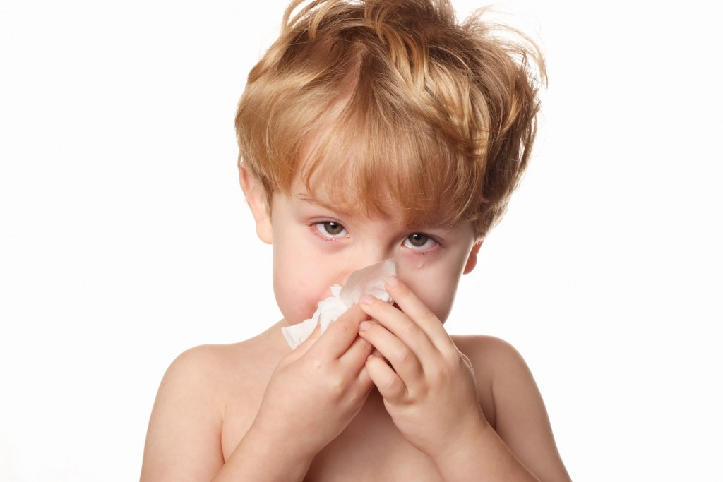 A sick young boy wiping his nose